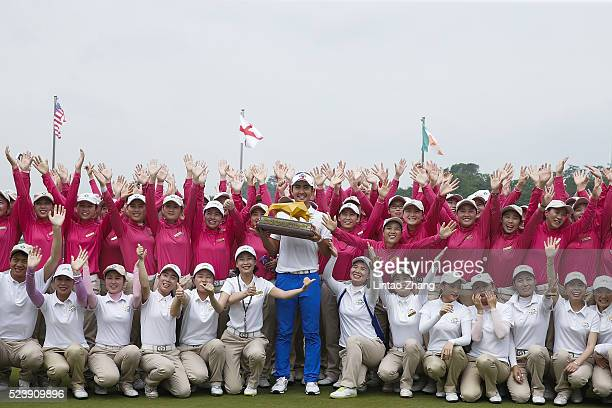Soomin Lee of South Korea holds the trophy with club caddy after winning the Shenzhen International at Genzon Golf Club on April 25 2016 in Shenzhen...