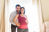 Portrait of smiling man hugging his beautiful pregnant wife at home