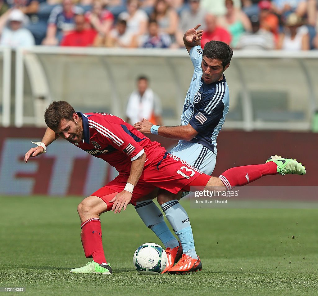Soony Saad #22 of Sporting Kansas City knocks down Gonzalo Segares #13 of the Chicago Fire during an MLS match at Toyota Park on July 7, 2013 in Bridgeview, Illinois. Sporting Kansas City defeated the Fire 2-1.