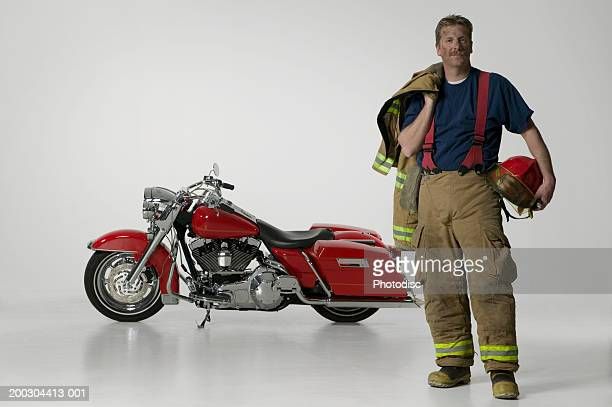 Sooty fireman standing by large red motorbike in studio, portrait