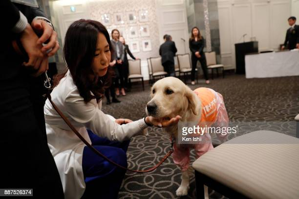 SooYun Kang of South Korea with an assistance dog during the Ladies Professional Golfers' Association of Japan induction ceremony at Hotel Monterey...