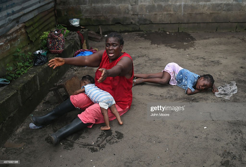 Sophia Doe sits with her grandchildren Beauty Mandi, 9 months (L) and Arthuneh Qunoh, 9, (R), while watching the arrival an Ebola burial team to take away the body of her daughter Mekie Nagbe, 28, for cremation on October 10, 2014 in Monrovia, Liberia. The children seen in the photo are daughters of the deceased. Mekie Nagbe, a market vendor died outside her home earlier in the morning while trying to walk to a treatment center, according to her relatives. The burial of loved ones is important in Liberian culture, making the removal of infected bodies for cremation all the more traumatic for surviving family members. The World Health Organization says the Ebola epidemic has now killed more than 4,000 people in West Africa.The woman had died outside her home earlier in the morning while trying to walk to a treatment center, according to her relatives. The burial of loved ones is important in Liberian culture, making the removal of infected bodies for cremation all the more traumatic for surviving family members.
