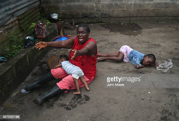 Sophia Doe sits with her grandchildren Beauty Mandi 9 months and Arthuneh Qunoh while watching the arrival an Ebola burial team to take away the body...