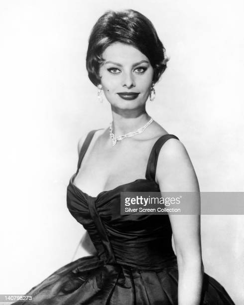 Sophia Loren Italian actress looking glamorous wearing a sleeveless lowcut black satin dress and a diamond necklace and diamond earrings in a studio...