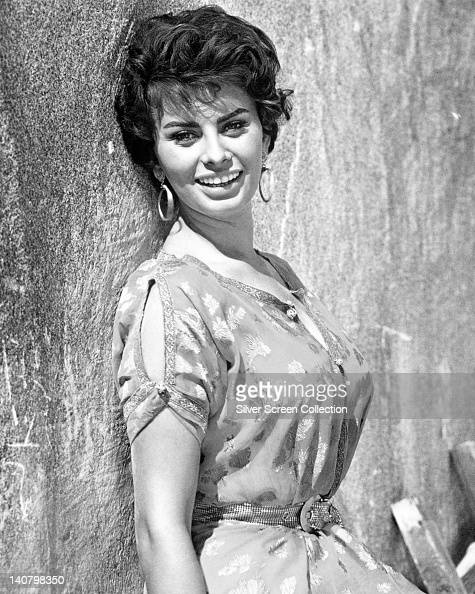 Sophia Loren Italian actress smiling and posing against a wall wearing a shortsleeve print pattern dress and large hoop earrings circa 1950