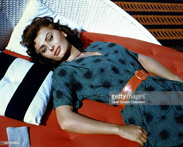 Sophia Loren Italian actress wearing a blue dress with a red belt reclining on a sun lounger circa 1960