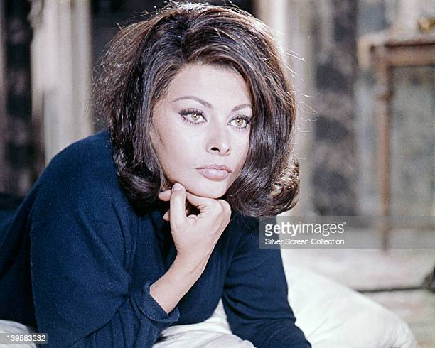 Sophia Loren Italian actress wearing a dark blue top posing with her chin resting on her right hand on a bed in an image issued as publicity for the...