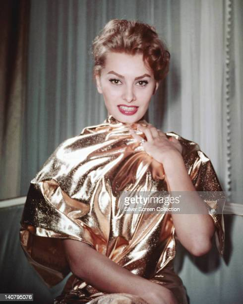 Sophia Loren Italian actress wearing a high neck metallic gold dress in a studio portrait circa 1960