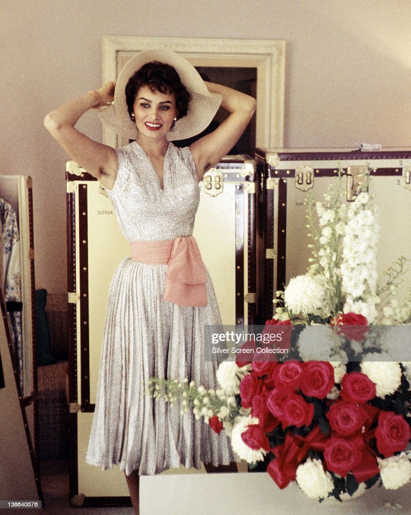 Sophia Loren, Italian actress, wearing a white sleeveless dress, with a pink sash around the waist, posing with a floppy-brimmed hat on her head, circa 1955.