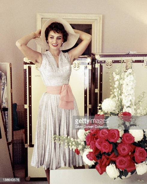 Sophia Loren Italian actress wearing a white sleeveless dress with a pink sash around the waist posing with a floppybrimmed hat on her head circa 1955