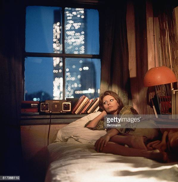 Sophia Loren reclining on a bed with a view of a window in the background showing a skyscraper illuminating the night sky Undated color slide