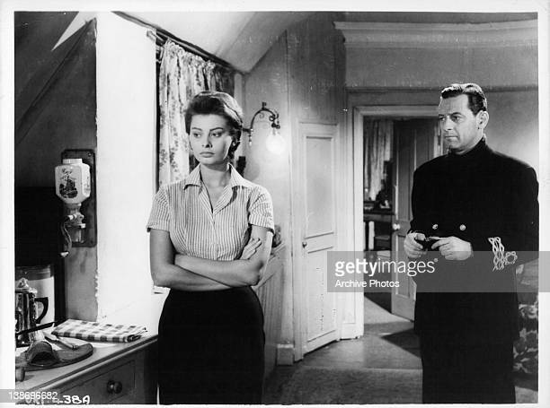 Sophia Loren with arms folded as William Holden looks at her in a scene from the film 'The Key' 1958