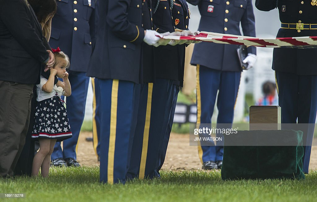 Sophia Phillips (L) plugs her ears as the firing party fires three rifle volleys for her father US Army Staff Sergeant Francis G. Phillips IV, as members of the US Army honor guard perform a full military honors burial service at Arlington National Cemetery in Arlington, Virginia on May 20, 2013.