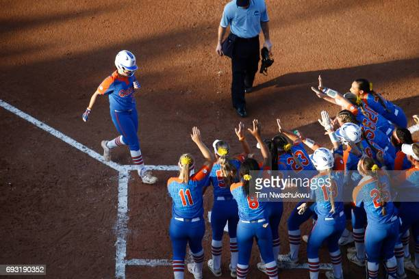 Sophia Reynoso of the University of Florida meets her celebrating team at home plate as they square off against the University of Oklahoma during...