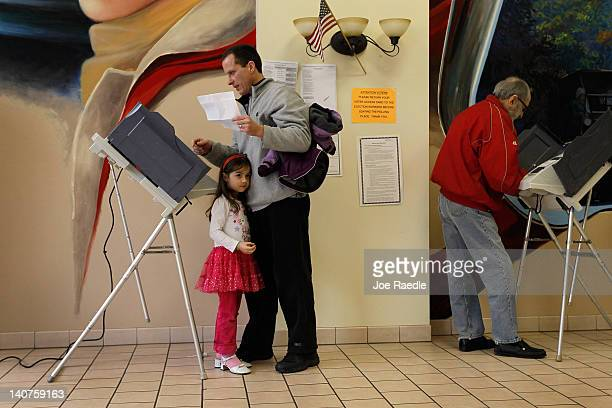 Sophia Walsh stans with her father William Walsh as he fills out his ballot at a polling station setup in Froehlich's Classic Corner as Ohio heads to...