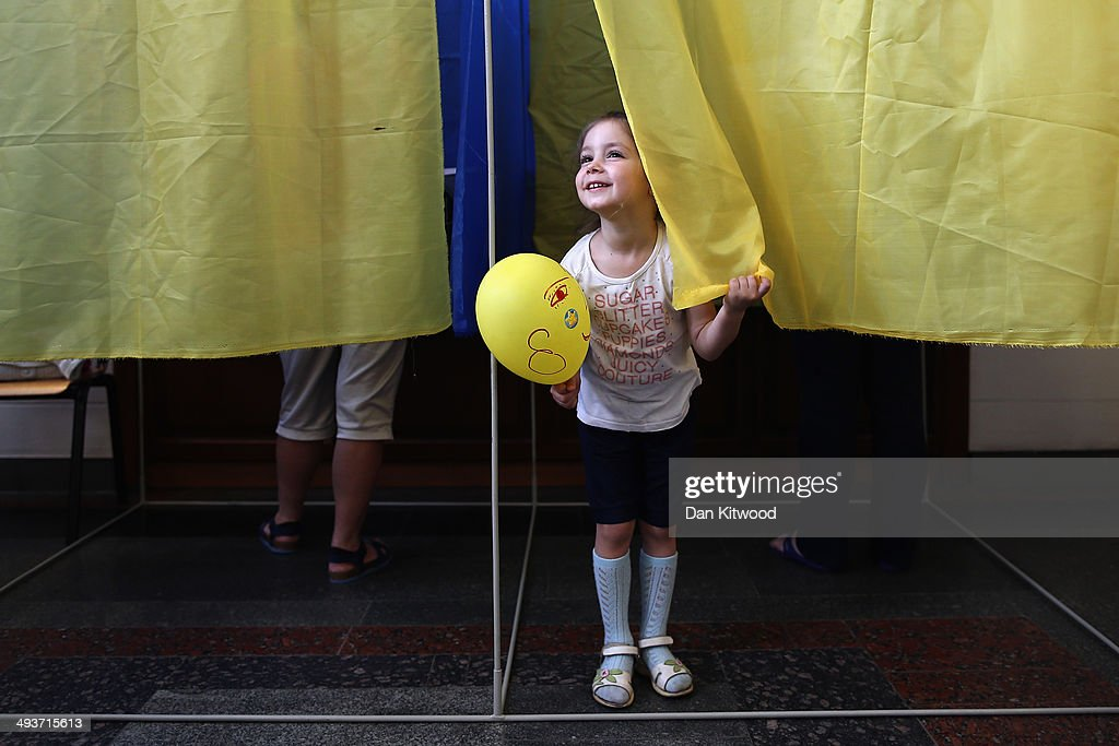 Sophie 4, waits for her mother to cast her vote in a polling booth on May 25, 2014 in Kiev, The Ukrainian Presidential election is taking place today.