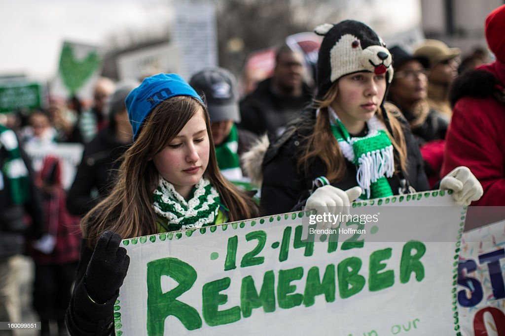 Sophie Ackert (L) and Maya Neuhoff, both 13 and from Newtown, Connecticut, march for stricter gun control laws on January 26, 2013 in Washington, DC. Demonstrators included survivors of the shooting at Virginia Tech, Newtown, Connecticut, and others.