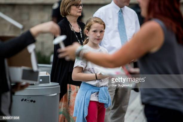Sophie Cass hands out candles at the Ascend Amphitheater for a vigil honoring the victims of the mass shooting in Las Vegas on October 2 2017 in...