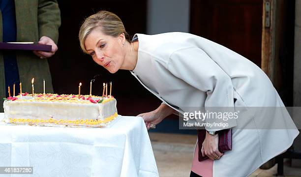 Sophie Countess of Wessex blows out the candles on her birthday cake as she and Prince Edward Earl of Wessex visit the Tomorrow's People Social...