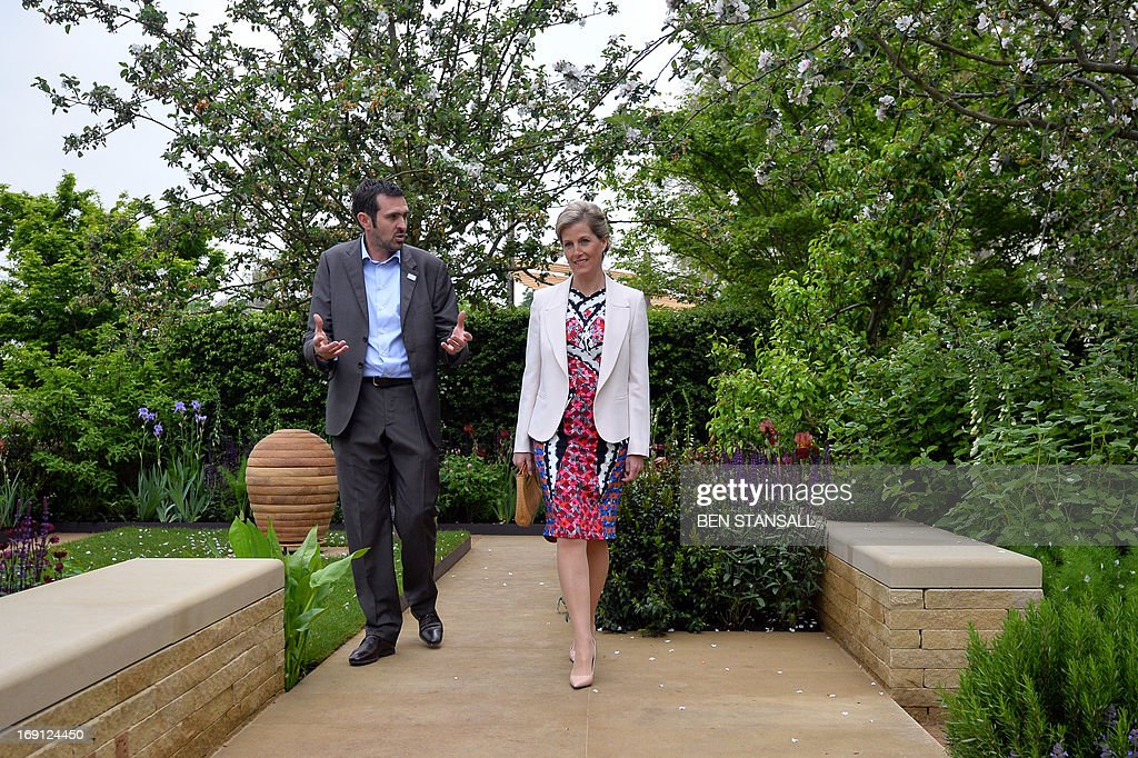 Sophie, Countess of Wessex (R), listens to garden designer Adam Frost (L) in the Homebase Garden during a visit to the Chelsea Flower Show in London on May 20, 2013. The world-famous gardening event run by the Royal Horticultural Society (RHS) is celebrating its centenary year. AFP PHOTO / BEN STANSALL