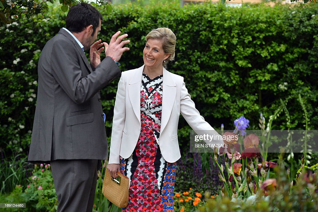 Sophie, Countess of Wessex (R), listens to garden designer Adam Frost (L) in the Homebase Garden during a visit to the Chelsea Flower Show in London on May 20, 2013. The world-famous gardening event run by the Royal Horticultural Society (RHS) is celebrating its centenary year.