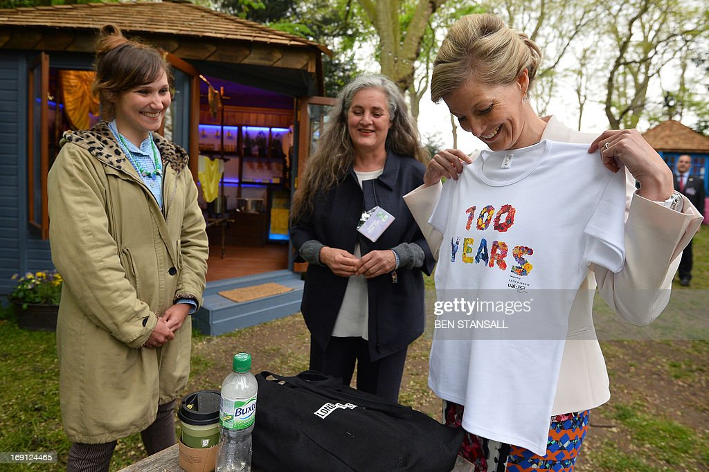 Sophie, Countess of Wessex (R), looks at a t-shirt presented to her by London College of Fashion course leader Susan Postlewaite (C) and London College of Fashion student Anya Crab (L) in the Homebase Garden during a visit to the Chelsea Flower Show in London on May 20, 2013. The world-famous gardening event run by the Royal Horticultural Society (RHS) is celebrating its centenary year.