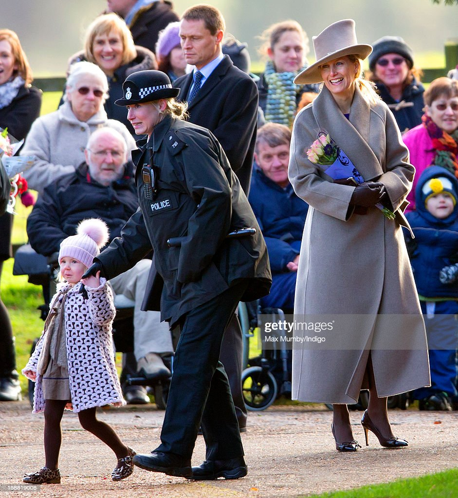 Sophie, Countess of Wessex looks on as a policewoman escorts a young girl who presented Queen Elizabeth II with a bunch of flowers as she left St. Mary Magdalene Church, Sandringham after attending Sunday service on December 30, 2012 near King's Lynn, England.