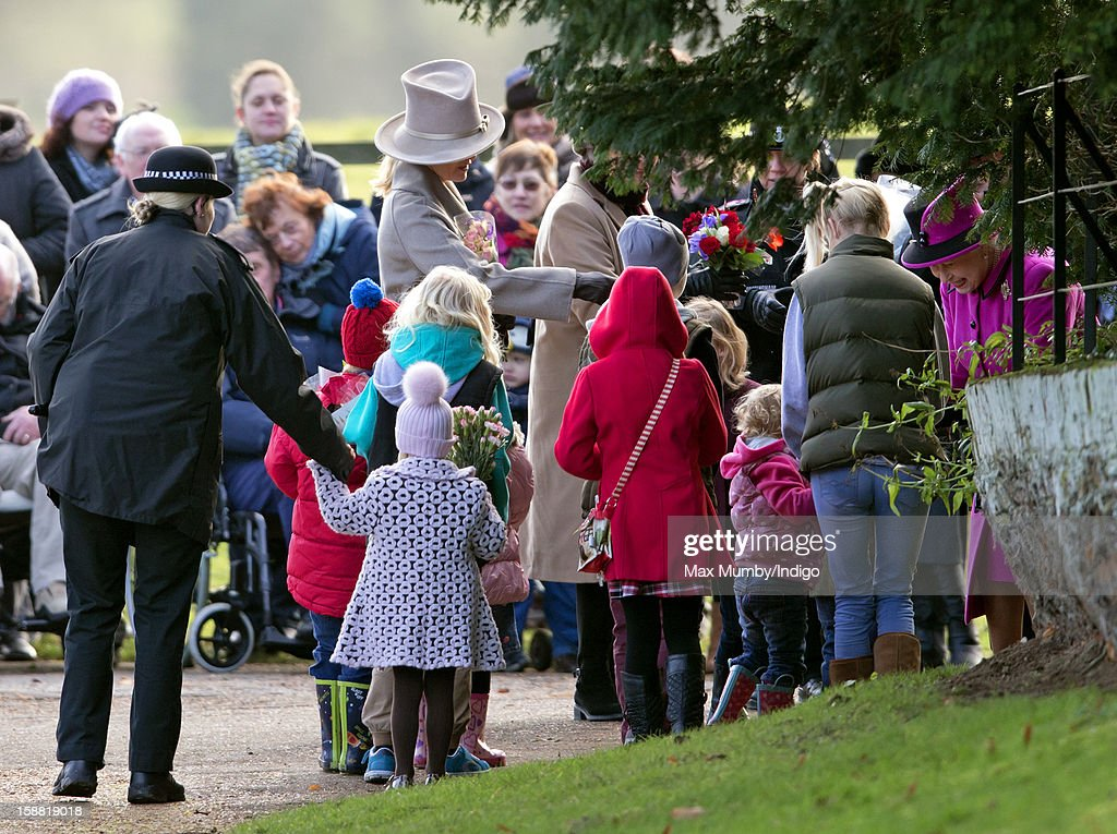 Sophie, Countess of Wessex (C) looks on as a policewoman escorts a young girl to present Queen Elizabeth II (R) with a bunch of flowers as she leaves St. Mary Magdalene Church, Sandringham after attending Sunday service on December 30, 2012 near King's Lynn, England.