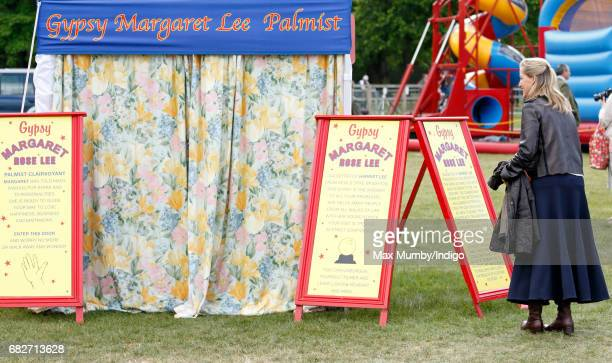 Sophie Countess of Wessex reads Palmist Gypsy Margaret Lee's advertising board as Autumn Phillips has her palm read on day 4 of the Royal Windsor...