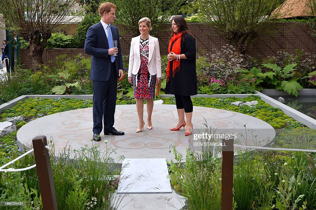 Sophie, Countess of Wessex (C), speak with Britain's Prince Harry (L) and garden designer Jinny Blum (R) in the B&Q Sentebale Forget-Me-Not garden during a visit visits to the Chelsea Flower Show in London on May 20, 2013. The world-famous gardening event run by the Royal Horticultural Society (RHS) is celebrating its centenary year.