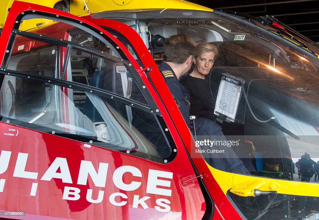 Sophie, Countess of Wessex speaks to pilot Dave Webber in the cockpit of an Air Ambulance during a visit to officially open the new air operating base at Thames Valley Air at RAF Benson on May 11, 2015 in Benson, England.