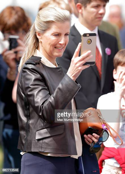 Sophie Countess of Wessex takes photographs of her son James Viscount Severn playing on an inflatable slide on day 4 of the Royal Windsor Horse Show...