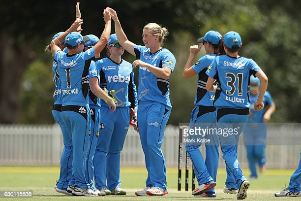 Sophie Devine of the Strikers celebrates with her team mates after taking the wicket of Stafanie Taylor of the Thunder during the WBBL match between...
