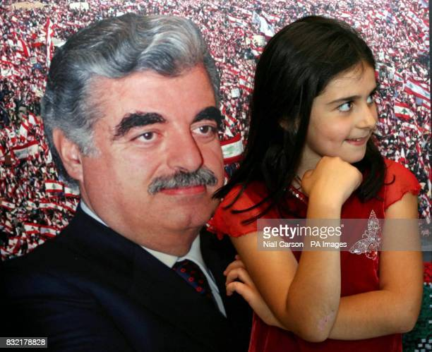 Sophie Jones from Lebanon stands in front of a portrait of assassinated Lebanese Prime Minister Rafik Hariri during the opening of a photographic...
