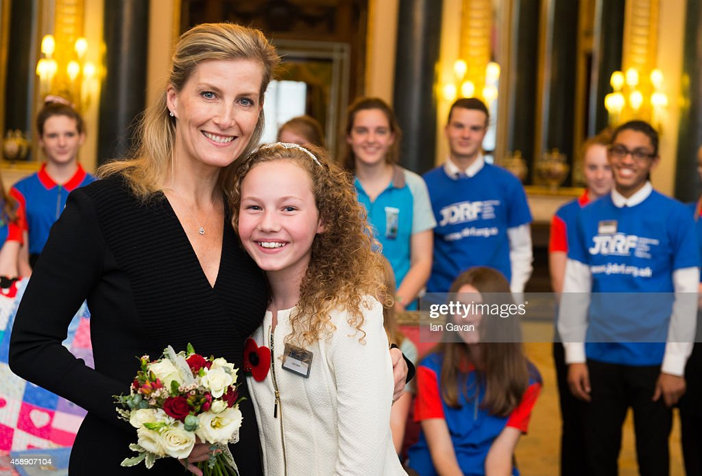 Sophie RhysJones Countess of Wessex receives a bouquet of flowers from Lucy Upton during a Guides reception in the Music Room at Buckingham Palace on...
