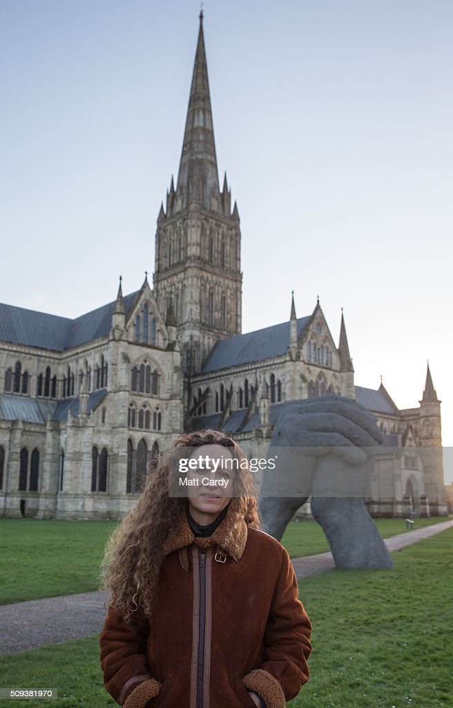 Sophie Ryder poses for a photograph in front of her sculpture The Kiss, that has been installed in the grounds of Salisbury Cathedral as part of an exhibition by the artist on February 10, 2016 in Salisbury, England. The solo exhibition, Relationships, featuring life-sized Minotaurs, Lady Hares and giant 20ft high clasped hands installed in and around the historic Cathedral, opens on February 12 and runs until July 3