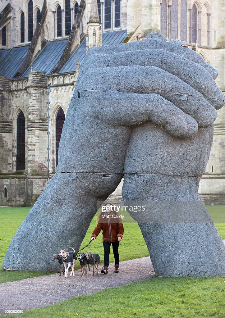 Sophie Ryder walks with her dogs in front of her sculpture The Kiss, that has been installed in the grounds of Salisbury Cathedral as part of an exhibition by the artist on February 10, 2016 in Salisbury, England. The solo exhibition, Relationships, featuring life-sized Minotaurs, Lady Hares and giant 20ft high clasped hands installed in and around the historic Cathedral, opens on February 12 and runs until July 3