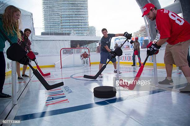 Sophie Shore left Stephen Kirsh Adam Ross and Ben Boudreau try to gain control of a giant puck in a life size table hockey arena at World Cup of...