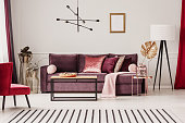 Gold leaf on copper table in sophisticated living room interior with striped carpet and violet sofa