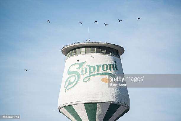 A Soproni logo sits on the side of a tower as birds fly over at the Heineken Hungaria Breweries Plc Sopron brewery in Sopron Hungary on Thursday Nov...