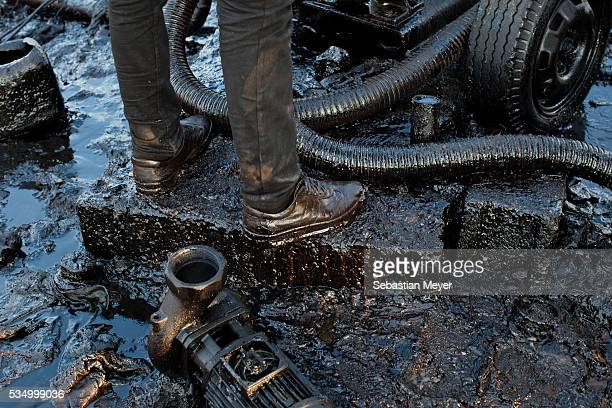 Sorbets stands in oil as he sets the electric pump to fill a waiter tanker The family of Yezidis displaced from Sinjar live next to an oil refinery...