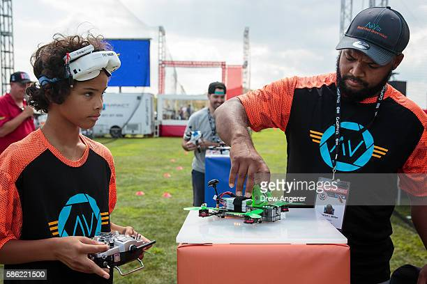 Sorell Miller and his father Conrad Miller prepare a drone on the starting block during practice day at the National Drone Racing Championships on...
