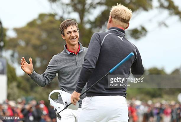 Soren Kjeldsen and Thorbjorn Olesen of Denmark celebrate on the 18th hole after winning during day four of the World Cup of Golf at Kingston Heath...