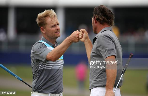 Soren Kjeldsen of denmark and Alex Cejka of Germany react after putting on the 18th green during the second round of the Zurich Classic at TPC...
