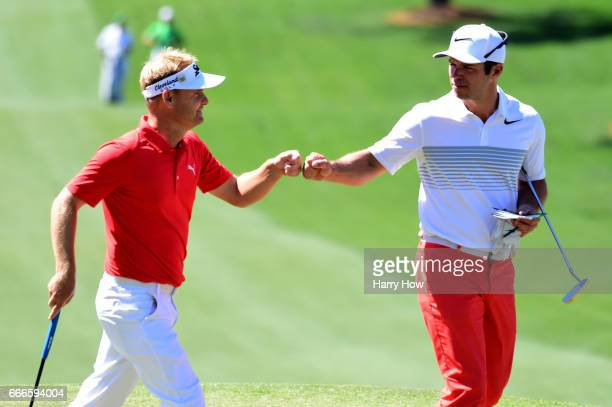 Soren Kjeldsen of Denmark and Paul Casey of England fistbump on the seventh green during the final round of the 2017 Masters Tournament at Augusta...