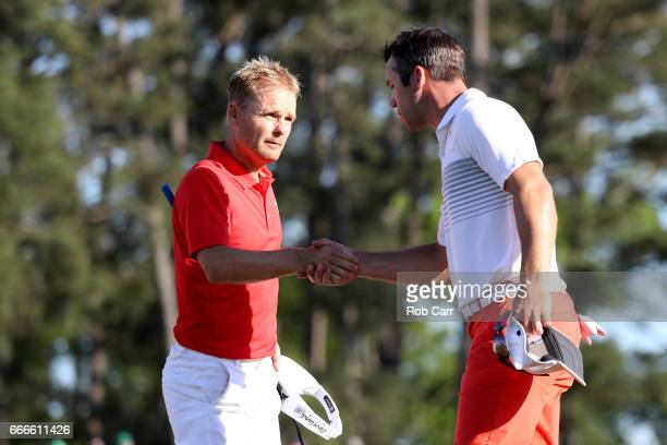 Soren Kjeldsen of Denmark and Paul Casey of England shake hands on the 18th green during the final round of the 2017 Masters Tournament at Augusta...