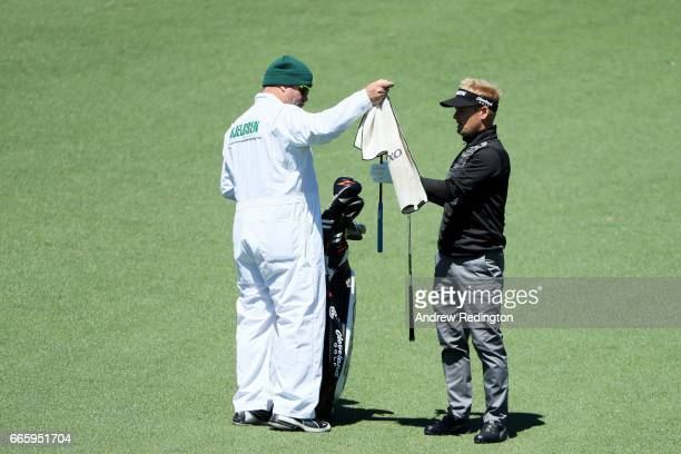 Soren Kjeldsen of Denmark cleans off his clubs with Alistair Matheson during the second round of the 2017 Masters Tournament at Augusta National Golf...