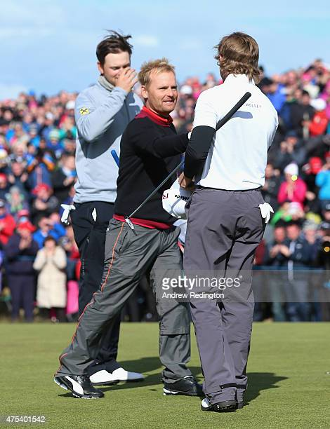 Soren Kjeldsen of Denmark is congratulated by Bernd Wiesberger of Austria and Eddie Pepperell of England after his victory in a playoff on the 18th...