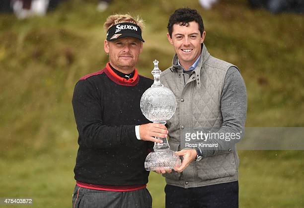 Soren Kjeldsen of Denmark receives the trophy from Rory McIlroy of Northern Ireland after his victory in a playoff during the Final Round of the...