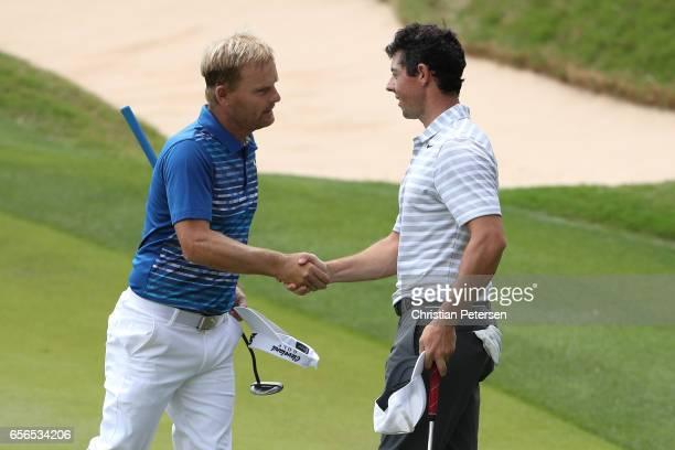 Soren Kjeldsen of Denmark shakes hands with Rory McIlroy of Northern Ireland after winning their match during round one of the World Golf...